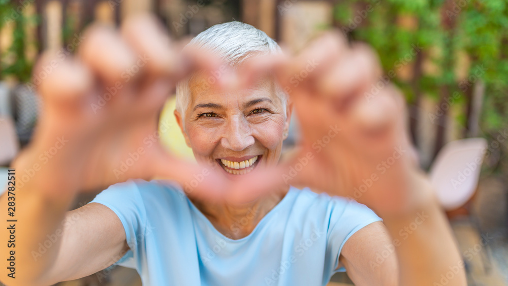 Fototapeta Cute senior old woman making a heart shape with her hands and fingers. Perfect, nice, aged, old, pretty woman, lover in t-shirt making, showing heart figure with fingers, looking at camera