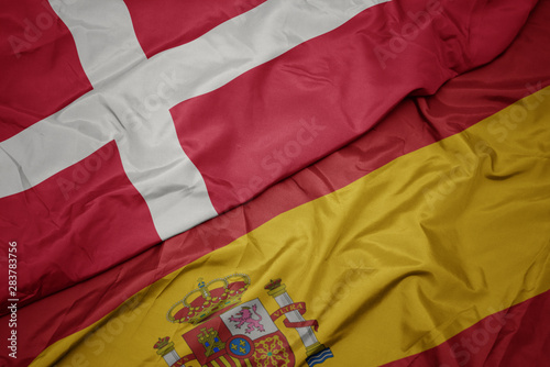 waving colorful flag of spain and national flag of denmark. Canvas Print
