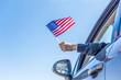 Leinwanddruck Bild - Boy holding Flag of America from the open car window on the sky background. USA.Concept