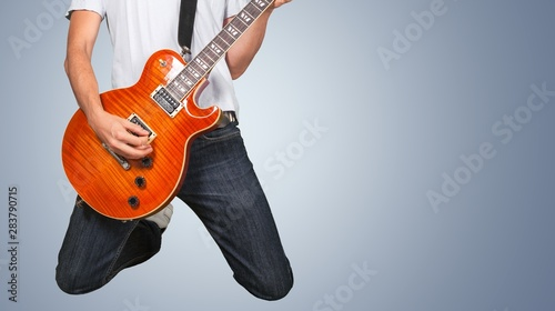Male Guitarist playing music on grey wall background - 283790715