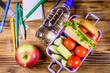 Bottle of water, ripe apple, different stationeries and lunch box with hamburger, cucumbers and tomatoes on wooden table. Top view