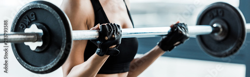 Fotografie, Obraz  panoramic shot of woman working out with barbell in gym