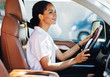 canvas print picture - Confident young woman driving car. Side view of female holding a steering wheel.