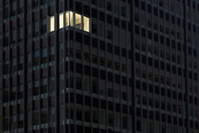 Corner Office With Lights On And Windows Glowing In A Darkened Office Building At Night Indicating Someone Working Overtime Late At Night