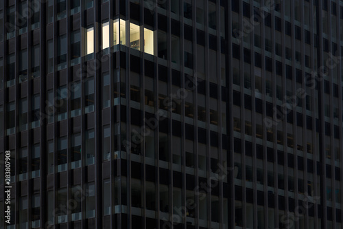Fotomural  Corner office with lights on and windows glowing in a darkened office building a