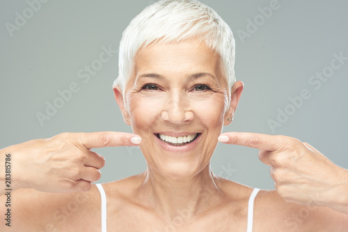 Beautiful Caucasian  smiling senior woman with short grey hair pointing at her teeth and looking at camera. Beauty photography. - 283815786