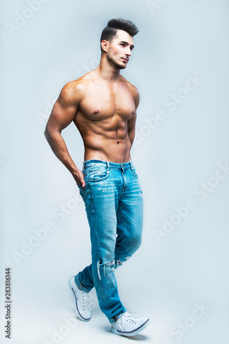 Carta da parati  Male model with perfect body in jeans posing over grey background