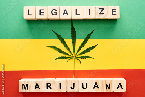 Fotografie, Obraz  top view of cannabis leaf and wooden blocks with legalize marijuana lettering on