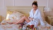 Close-up shot of a young woman in bathrobe enjoying coffee in the hotel room