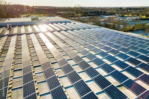 Top view of blue shiny solar photo voltaic panels system producing renewable clean energy abstract background.