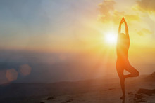 Young Women Meditate While Doing Yoga Meditation, Spiritual Mental Health Practice With Silhouette Of Lotus Pose Having Peaceful Mind Relaxation On Mountain Outdoor With Sunset Golden Heavenly.