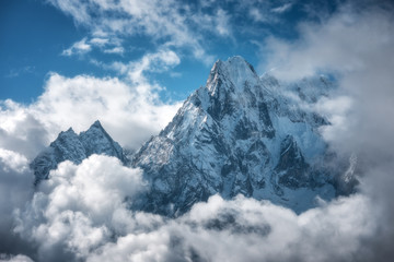 Naklejka Popularne Manaslu mountain with snowy peak in clouds in sunny bright day in Nepal. Landscape with high snow covered rocks and blue cloudy sky. Beautiful nature. Fairy scenery. Aerial view of Himalayan mountains