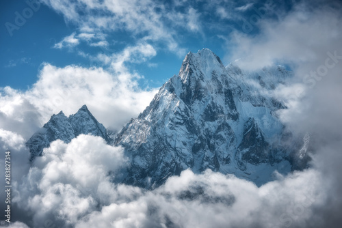 Obraz Manaslu mountain with snowy peak in clouds in sunny bright day in Nepal. Landscape with high snow covered rocks and blue cloudy sky. Beautiful nature. Fairy scenery. Aerial view of Himalayan mountains - fototapety do salonu