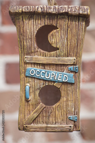 Fotografering Cute birdhouse labeled occupied