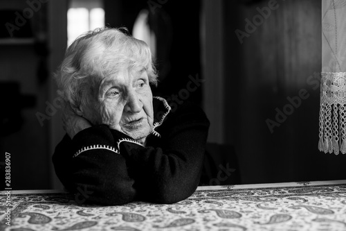 Lonely sad old woman. Black and white photo. Fototapete