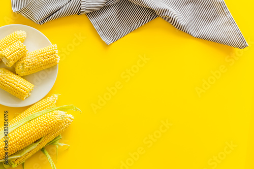 Fototapeta Ripe corn on cobs on plate on yellow table background top view mock up