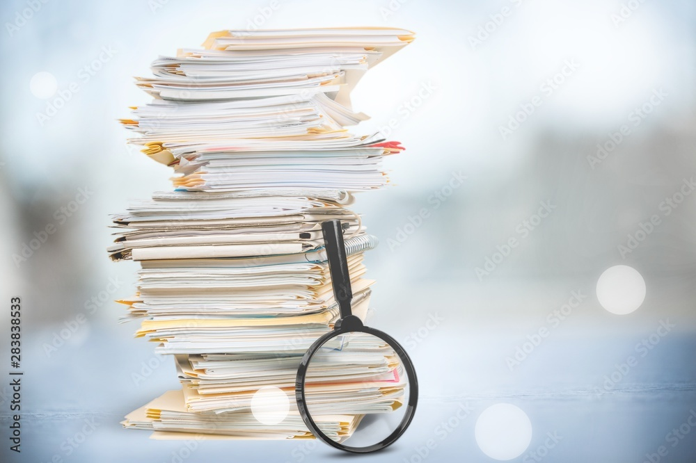 Fototapeta File folders with documents and magnifying glass on background