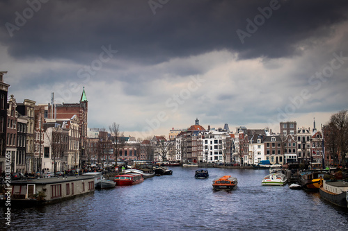 Photo  Amsterdam waterway with boats and buildings