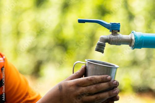 Cuadros en Lienzo  Water from tab pouring in hand on nature background, Concept for save water,cons