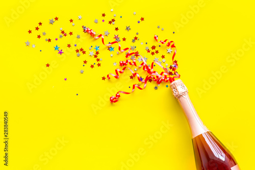 Party with champagne bottle and colorful party streamers on yellow background top view copy space