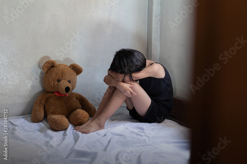 Sad little girl sitting in room. human trafficking concept. - 283841752
