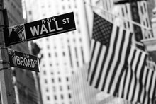 Wall Street Sign In New York City With American Flags And New York Stock Exchange In Background. Black And White Image.