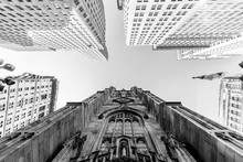 Wide Angle Upward View Of Trinity Church At Broadway And Wall Street With Surrounding Skyscrapers, Lower Manhattan, New York City, USA. Black And White Image.