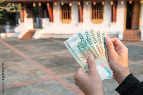 Canvas Prints Chicken Cropped shot view of someone holding banknotes of Laos kip money (100,000 kip) the national currency of Laos