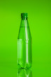 Leinwandbild Motiv Crystal clear water in a bottle on green background