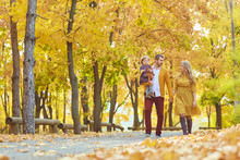 Family Walking In The Park In Yellow Autumn.
