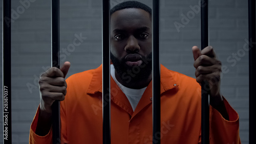 Photo  Black prisoner holding bars and looking at camera, drug dealer punishment
