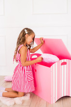 Cute Girl In A Beautiful Dress At Home Plays With A Decorative Chest And Toys