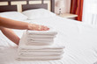Woman putting stack of fresh white bath clean towels on bed sheet, copy space. Close up hands of hotel maid with towels. Room service