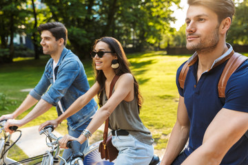 Group of happy friends riding bicycles at the park