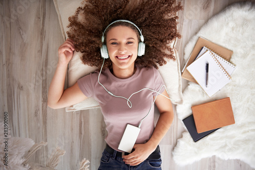 Portrait of smiling teenage girl listening to music - 283900960