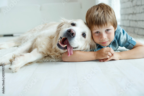Photo A child with a dog. Little boy with a dog at home.