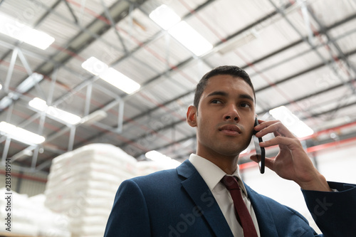 Businessman talking on mobile phone in warehouse