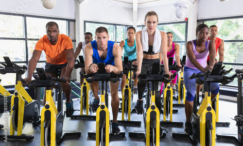 Fit people exercising on exercise bike in fitness center