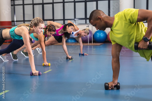 Male trainer training women to exercise with dumbbells