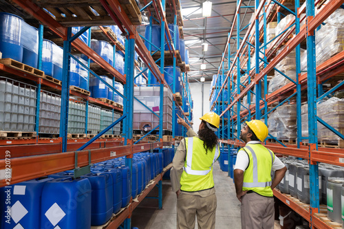 Female worker showing something to male worker in warehouse