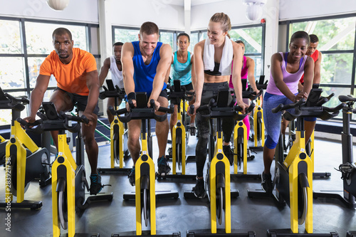 Fit people exercising on exercise bike in fitness center Fototapete