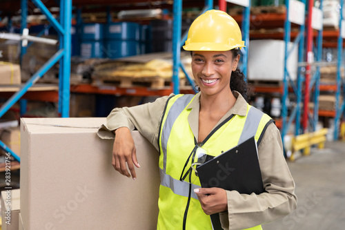 Foto Female staff smiling while standing in warehouse