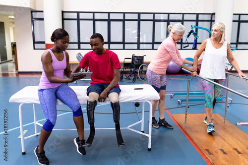 Female trainer helping and discussing with disabled man and woman in sports center