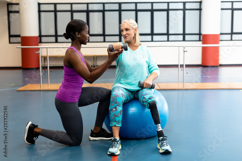 Trainer assisting disabled senior woman to exercise with dumbbell in sports center