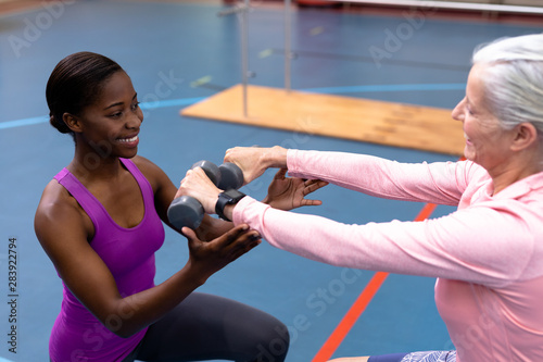 Female trainer assisting disabled senior woman to exercise with dumbbell in sports center