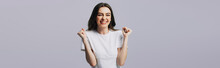 Excited Beautiful Girl In White T-shirt Showing Yes Gesture Isolated On Grey, Panoramic Shot