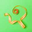 canvas print picture - Top view of curled measuring tape as a sewing accessory on green background. Tailor concept with copy space
