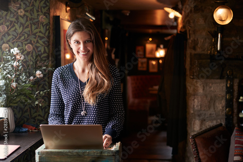 Vászonkép Portrait Of Female Receptionist Working On Laptop At Hotel Check In