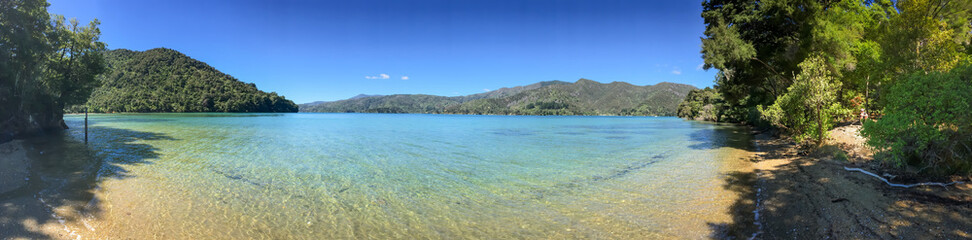 A shoreline level sweeping panoramic view of the beautiful Marlbough Sounds, New Zealand, sparkling waters, clear blue skies