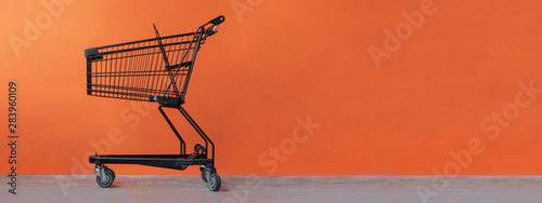 Shopping cart on an orange background Fototapeta